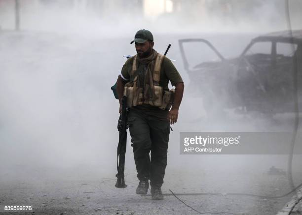 A fighter of the Hashed AlShaabi walks through the dust carrying a rocketpropelled grenade launcher during the advance through the town of Tal Afar...