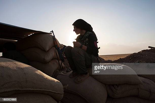 A fighter of the Kurdish of the Kurdish Women's Defense Units sits on sand bags as she holds a position on the front line on October 19 2013 in the...
