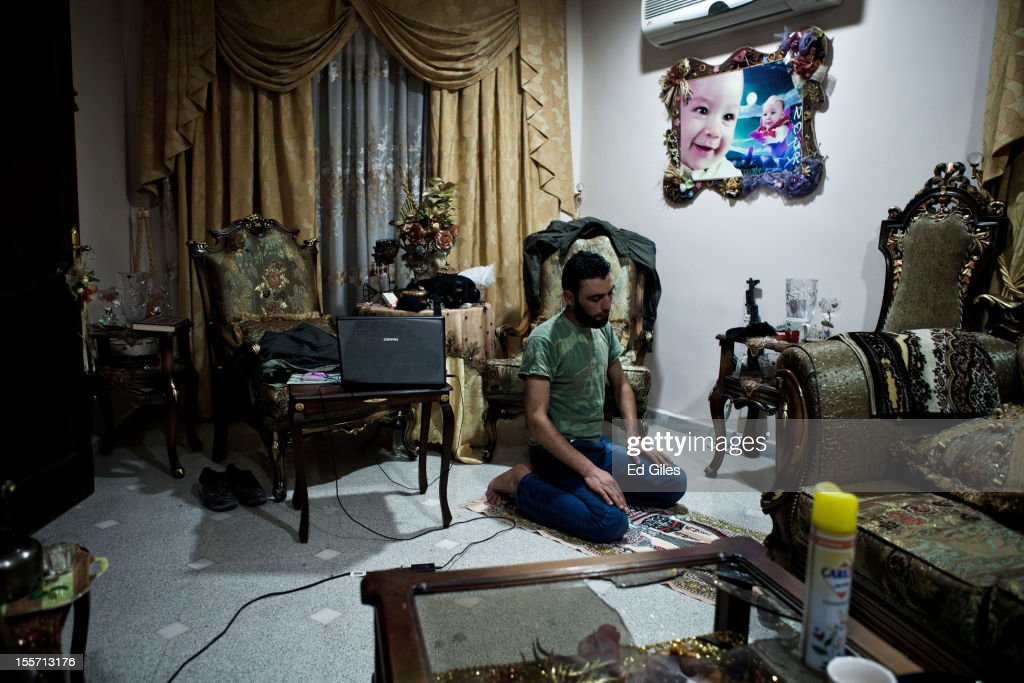 A fighter of the Shohada el Haq brigade of the Free Syrian Army performs evening prayers in an occupied apartment near the Salahudeen district on November 4, 2012 in Aleppo, Syria. The Shohada al Haq, or 'Martyrs of Truth' brigade control an area on the edge of the Salahudeen district in Aleppo, Syria's largest city. The brigade is made up of around 70 men, holding a handful of positions hidden in apartment blocks on the front line of Aleppo, facing toward Syrian army positions sometimes less than one hundred meters away. The Shohada al Haq use snipers to target Syrian regime troops as they move on the other side of the front, as well as moving between apartment blocks in the 'no man's land' between the two forces, occupying positions of advantage over the Syrian military. The brigade, or 'Katiba', live in the apartments they occupy, and the unit of rebel fighters is made up of former soldiers who defected from the Syrian military alongside men from Aleppo and other cities across Syria who have chosen to fight in Syria's increasingly violent civil war. (Photo by Ed Giles/Getty Images).