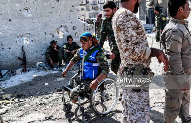 TOPSHOT A fighter of the Syrian Democratic Forces pushes his amputee comrade as they gather with others at the stadium in Raqa to celebrate on...