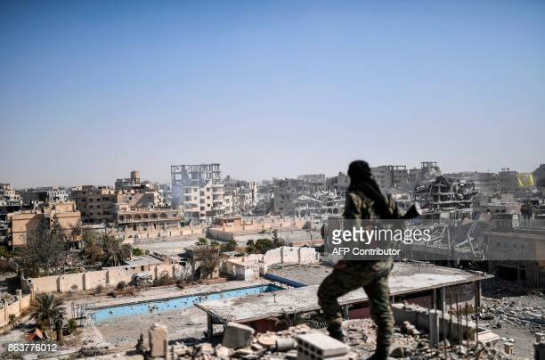 TOPSHOT A fighter of the Syrian Democratic Forces stands guard on a rooftop in Raqa on October 20 after retaking the city from Islamic State group...