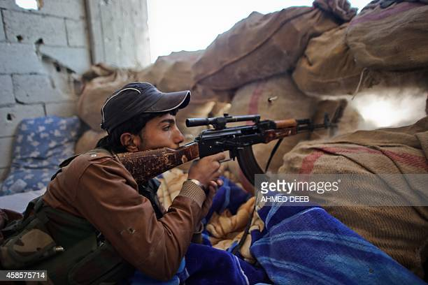 A fighter of the Syrian Kurdish People's Protection Units holds a position behind sanbags during fighting against Islamic State group on November 7...
