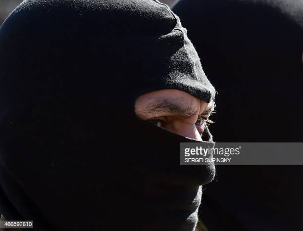 A fighter of the Ukrainian volonteer battalion 'Donbass' wears a black balaclava during a farewell ceremony in central Kiev on March 17 2015 prior to...