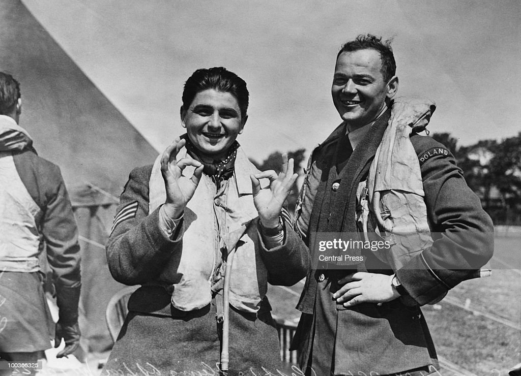 An RAF fighter station in England during the Battle of Britain, World War II, 16th August 1940. Two Polish pilots stationed with the RAF give the OK sign. On the left is Sergeant Glowacki, who has shot down one aircraft, whilst his companion has shot down two.