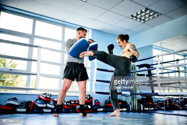 Fighter practicing kicks with personal trainer
