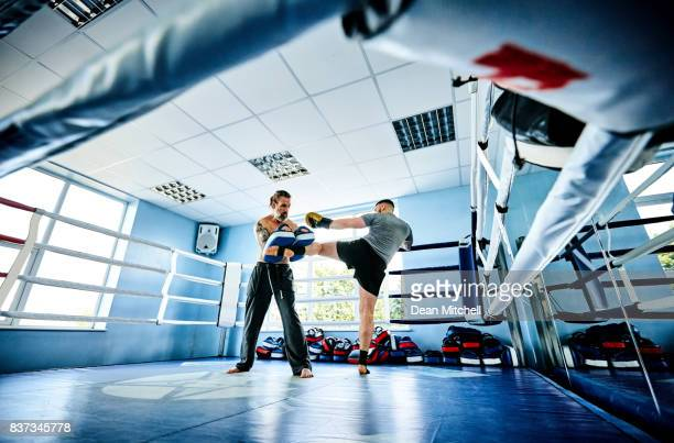 Fighter practicing some kicks with personal trainer