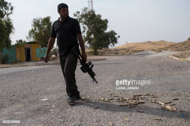 A fighter with the Iraqi Special Forces walks past debris bullet casings within the Mosel Dam complex the morning after Peshmerga and Iraqi Special...