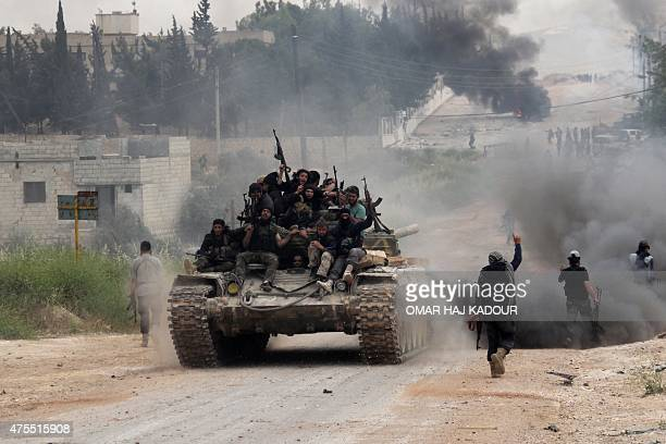 Fighters from a coalition of Islamist forces celebrate on May 19 2015 after taking the AlMastumah base in the Syrian city of Idlib the second...