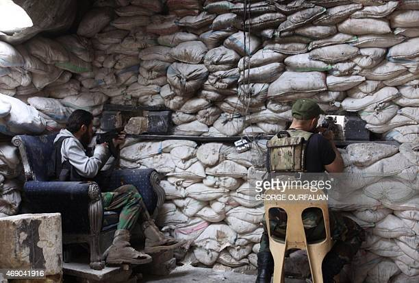 Fighters from a local popular committee who support the Syrian government forces guard a look out point in the Hamidiyeh neighbourhood of the...