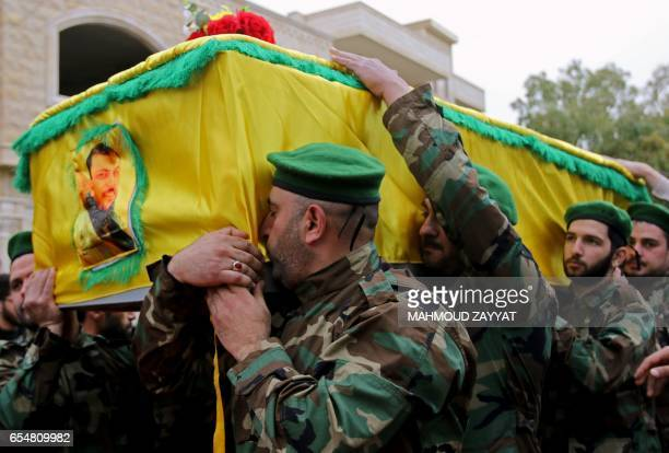 TOPSHOT Fighters from Lebanon's Shiite Hezbollah movement carry the coffin of a comrade who died in combat in Syria during his funeral in the...