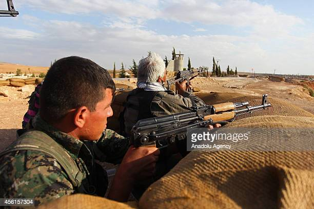 Fighters from People's Protection Units armed wing of Democratic Union Party take position behind piled sandbags in Ayn alArab district of Aleppo in...