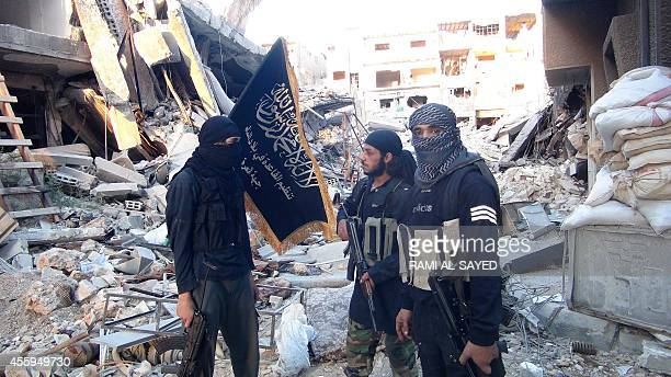 Fighters from the alQaida group in the Levant AlNusra Front stand among destroyed buildings near the front line with Syrian government solders in...