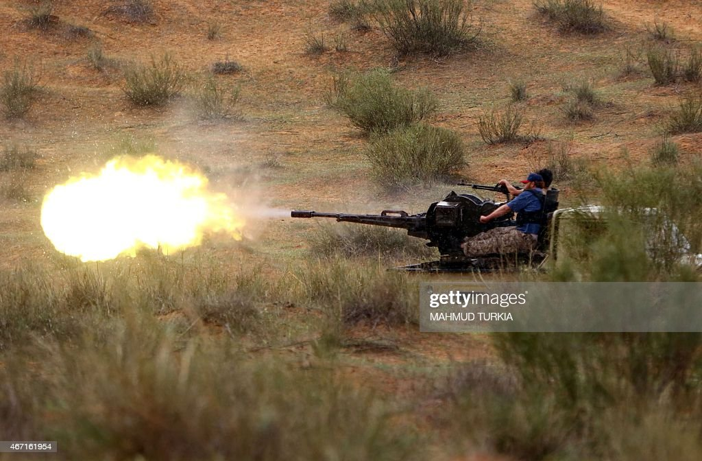 Fighters from the Fajr Libya an alliance of Islamistbacked militias fire a heavy machine gun mounted on a pickup truck towards an opposing militia...
