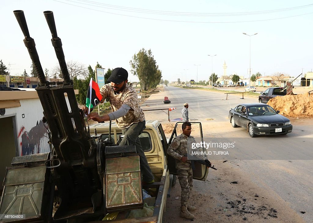 Fighters from the Fajr Libya an alliance of Islamistbacked militias man a checkpoint in alAziziyah located some 40 kilometres south of the Libyan...