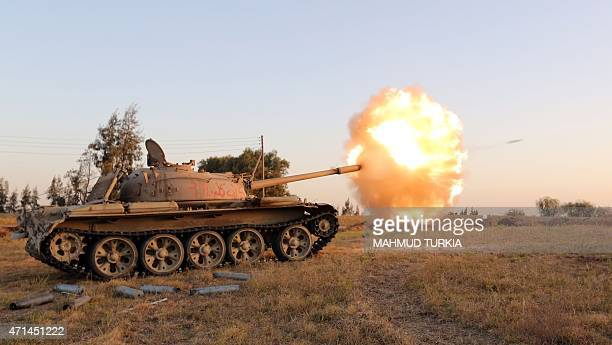 Fighters from the Fajr Libya militia fire shells from a tank during clashes with forces loyal to Libya's internationally recognised government...