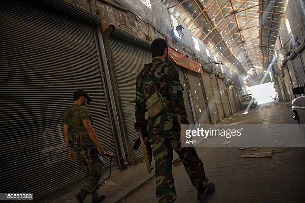 Fighters from the Free Syrian Army walk through a covered souq in the Old City of Syria's northern city of Aleppo on August 20 2012 The Old City a...