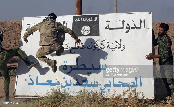 Fighters from the Hashed alShaabi backing the Iraqi forces kick a billboard bearing the logo of the Islamic State group in Hawija on October 6 a day...