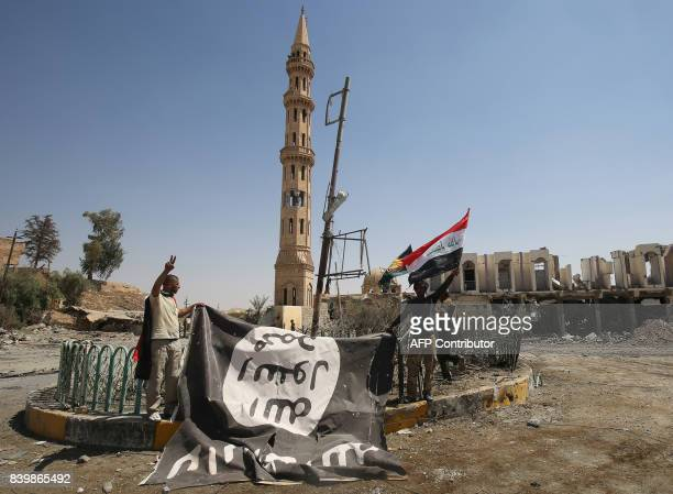 TOPSHOT Fighters from the Hashed alShaabi backing the Iraqi forces pose for a photograph with a flag of the Islamic State group in Tal Afar's Qalea...