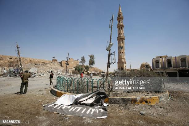 Fighters from the Hashed alShaabi backing the Iraqi forces stand next to a flag of the Islamic State group in Tal Afar's Qalea central district...