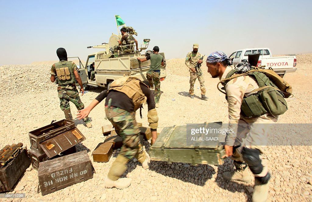 Fighters from the Iraqi Imam Ali Brigade carry artillery during heavy clashes with Islamic State militants in Tuz Khurmatu in Salaheddin province...