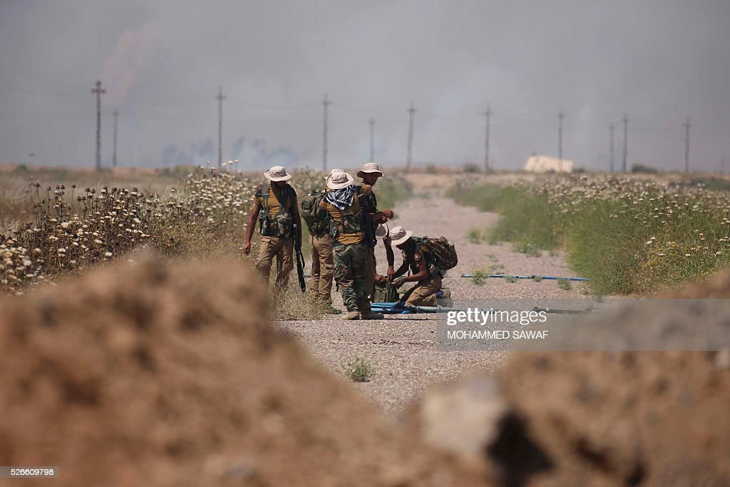 Fighters from the Iraqi pro-government forces load their weapons during an operation to retake the town of al-Bashir, near Kirkuk, from the Islamic State group (IS), on April 30, 2016. Iraqi forces launched a final assault Saturday to retake the Turkmen majority town of Bashir from the Islamic State jihadist group, Kurdish authorities said. 'Bashir village is surrounded and 80 percent has been cleared,' the Kurdistan Region Security Council said on social media. Turkmen units from Iraq's Hashed al-Shaabi (Popular Mobilisation) militia umbrella group, which announced an operation to retake the town earlier this month, were also taking part. / AFP / Mohammed SAWAF