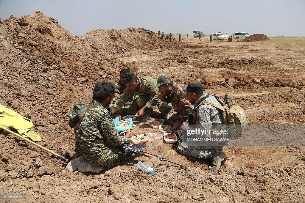 Fighters from the Iraqi pro-government forces take a break during an operation to retake the town of al-Bashir, near Kirkuk, from the Islamic State group (IS), on April 30, 2016. Iraqi forces launched a final assault Saturday to retake the Turkmen majority town of Bashir from the Islamic State jihadist group, Kurdish authorities said. 'Bashir village is surrounded and 80 percent has been cleared,' the Kurdistan Region Security Council said on social media. Turkmen units from Iraq's Hashed al-Shaabi (Popular Mobilisation) militia umbrella group, which announced an operation to retake the town earlier this month, were also taking part. / AFP / Mohammed SAWAF