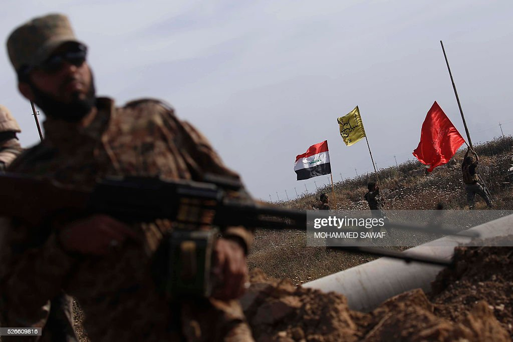 Fighters from the Iraqi pro-government forces take position during an operation to retake the town of al-Bashir, near Kirkuk, from the Islamic State group (IS), on April 30, 2016. Iraqi forces launched a final assault Saturday to retake the Turkmen majority town of Bashir from the Islamic State jihadist group, Kurdish authorities said. 'Bashir village is surrounded and 80 percent has been cleared,' the Kurdistan Region Security Council said on social media. Turkmen units from Iraq's Hashed al-Shaabi (Popular Mobilisation) militia umbrella group, which announced an operation to retake the town earlier this month, were also taking part. / AFP / Mohammed SAWAF