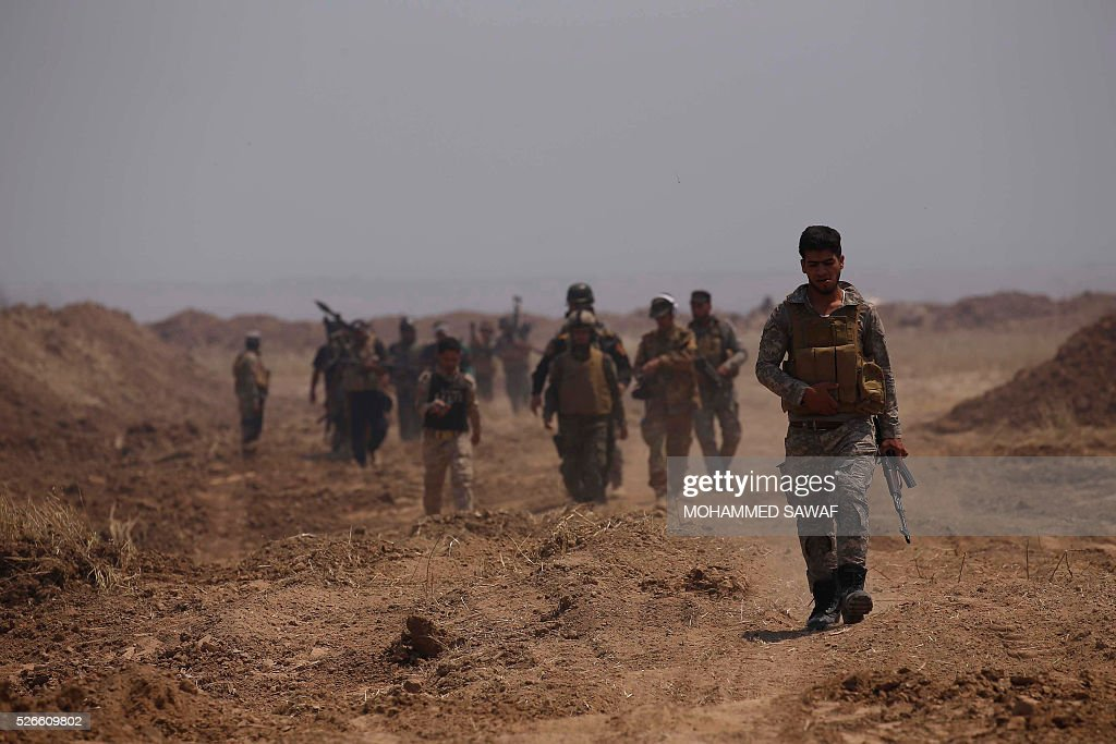 Fighters from the Iraqi pro-government forces walk down a road as they head towards the town of al-Bashir, near Kirkuk, during an operation to retake it from the Islamic State group (IS), on April 30, 2016. Iraqi forces launched a final assault Saturday to retake the Turkmen majority town of Bashir from the Islamic State jihadist group, Kurdish authorities said. 'Bashir village is surrounded and 80 percent has been cleared,' the Kurdistan Region Security Council said on social media. Turkmen units from Iraq's Hashed al-Shaabi (Popular Mobilisation) militia umbrella group, which announced an operation to retake the town earlier this month, were also taking part. / AFP / Mohammed SAWAF