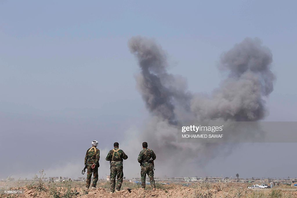 Fighters from the Iraqi pro-government forces watch smoke billow during an operation to retake the town of al-Bashir, near Kirkuk, from the Islamic State group (IS), on April 30, 2016. Iraqi forces launched a final assault Saturday to retake the Turkmen majority town of Bashir from the Islamic State jihadist group, Kurdish authorities said. 'Bashir village is surrounded and 80 percent has been cleared,' the Kurdistan Region Security Council said on social media. Turkmen units from Iraq's Hashed al-Shaabi (Popular Mobilisation) militia umbrella group, which announced an operation to retake the town earlier this month, were also taking part. / AFP / Mohammed SAWAF