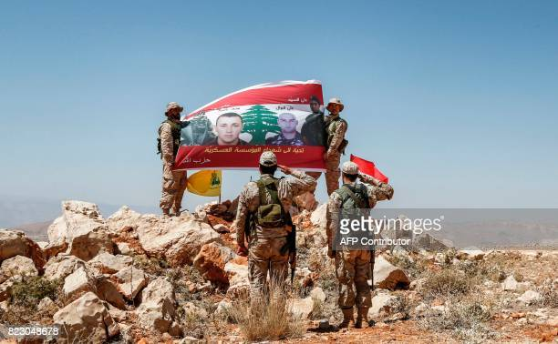Fighters from the Lebanese Shiite Hezbollah movement raise up and salute a banner in a mountainous area around the Lebanese border town of Arsal...