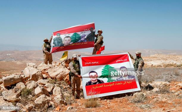 Fighters from the Lebanese Shiite Hezbollah movement raise up banners in a mountainous area around the Lebanese border town of Arsal during a tour...