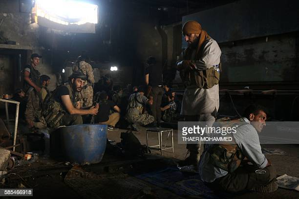 Fighters from the opposition forces pray and rest in a building on August 2 2016 as they battle in the Ramouse industrial neighbourhood on the...