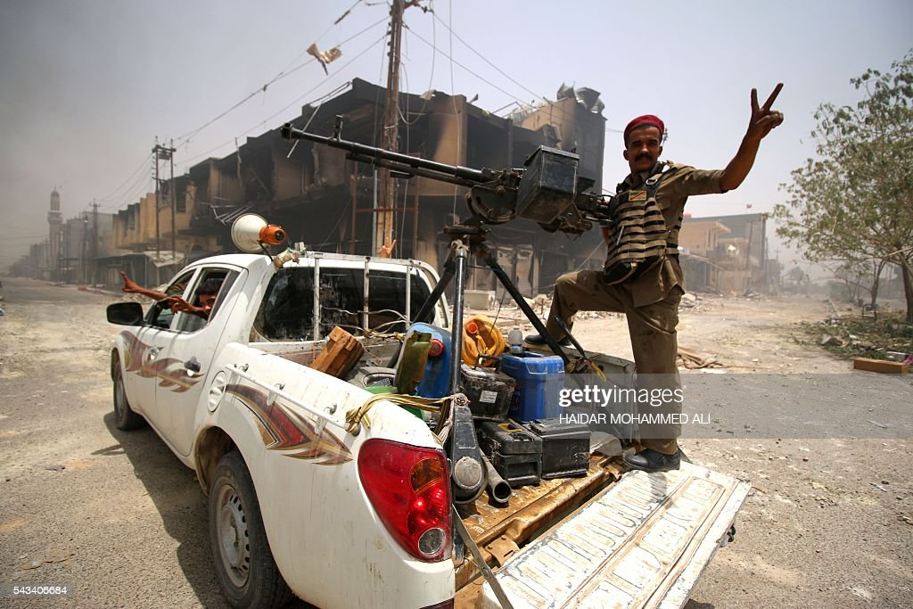 Fighters from the Popular Mobilisation units supporting the government forces flash the V-sign for 'Victory' as they patrol a street in Fallujah on June 28, 2016, after Iraqi forces retook the city from the Islamic State group. Iraqi forces took the Islamic State group's last positions in Fallujah on June 26, 2016, establishing full control over one of the jihadists' most emblematic bastions after a month-long operation. / AFP / HAIDAR