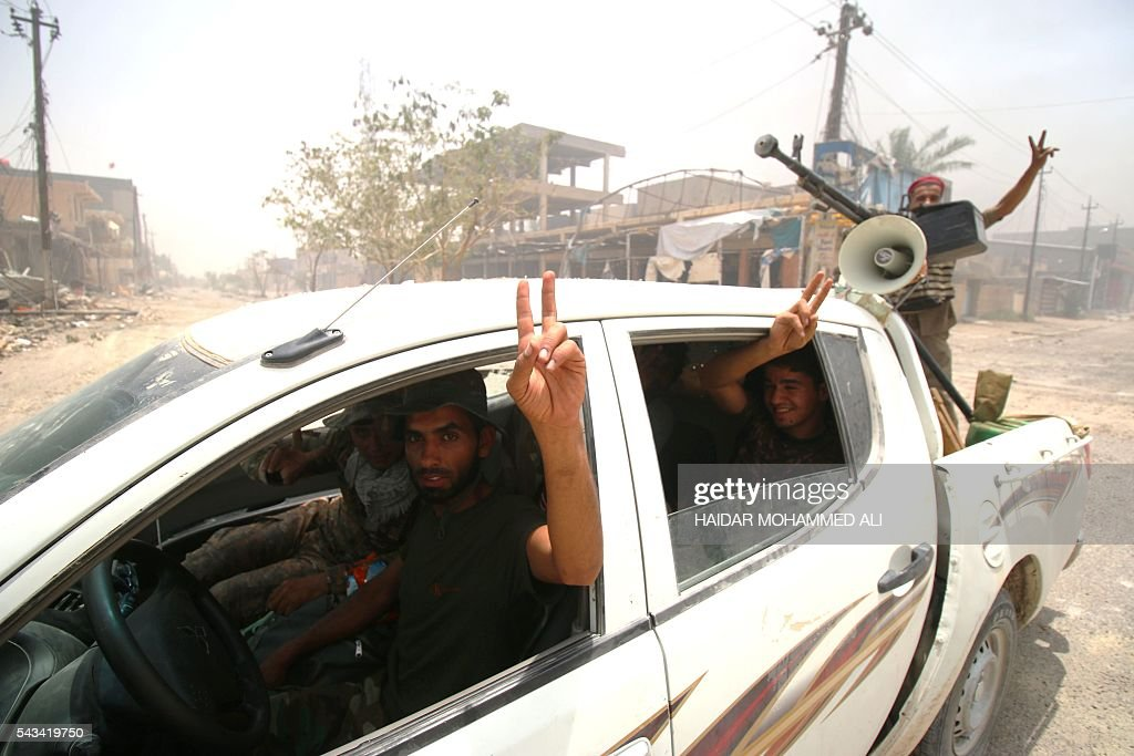 Fighters from the Popular Mobilisation units, supporting the government forces, flash the V-sign for 'Victory' as they patrol a street in Fallujah on June 28, 2016, after Iraqi forces retook the city from the Islamic State group. Iraqi forces took the Islamic State group's last positions in Fallujah on June 26, 2016, establishing full control over one of the jihadists' most emblematic bastions after a month-long operation. / AFP / HAIDAR