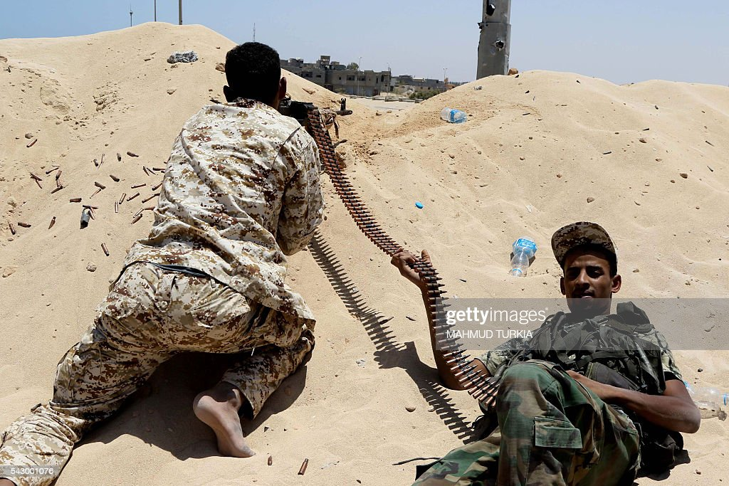 Fighters from the pro-government forces loyal to Libya's Government of National Unity (GNA) hold a position in Sirte during an operation to recapture the costal city from Islamic State group jihadists on June 25, 2016. The jihadists overran the city some 450 kilometres (270 miles) east of the capital Tripoli in June last year. Since May 12, 2016, pro-government forces from the west, Libyan naval forces and eastern militias have pushed IS militants back into a residential zone of just five square kilometres (two square miles) inside the city. / AFP / MAHMUD