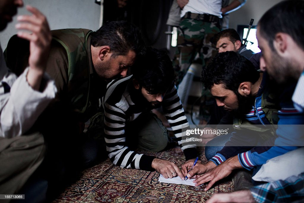 Fighters from the Shohada al Haq brigade discuss tactics during a planning meeting in an occupied apartment near the Salahudeen district on November 6, 2012 in Aleppo, Syria. The Shohada al Haq, or 'Martyrs of Truth' brigade control an area on the edge of the Salahudeen district in Aleppo, Syria's largest city. The brigade is made up of around 70 men, holding a handful of positions hidden in apartment blocks on the front line of Aleppo, facing toward Syrian army positions sometimes less than one hundred meters away. The Shohada al Haq use snipers to target Syrian regime troops as they move on the other side of the front, as well as moving between apartment blocks in the 'no man's land' between the two forces, occupying positions of advantage over the Syrian military. The brigade, or 'Katiba', live in the apartments they occupy, and the unit of rebel fighters is made up of former soldiers who defected from the Syrian military alongside men from Aleppo and other cities across Syria who have chosen to fight in Syria's increasingly violent civil war. (Photo by Ed Giles/Getty Images).