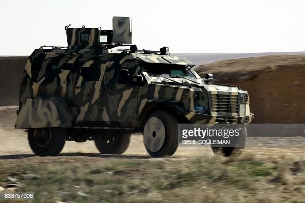 Fighters from the Syrian Democratic Forces drive a military vehicle supplied by the USled coalition as they gather near a village northeast of Raqa...
