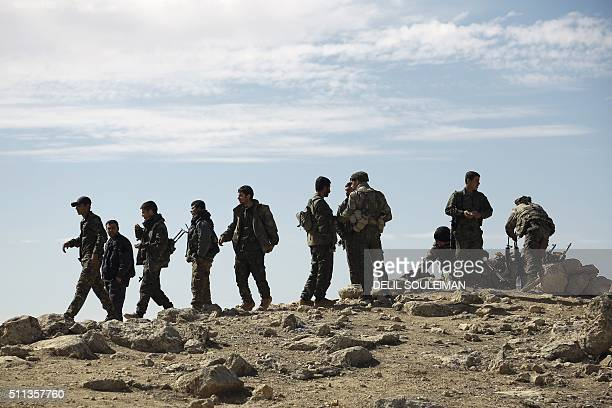 Fighters from the Syrian Democratic Forces gather on the outskirts of the town of alShadadi in the northeastern Syrian province of Hasakeh on...