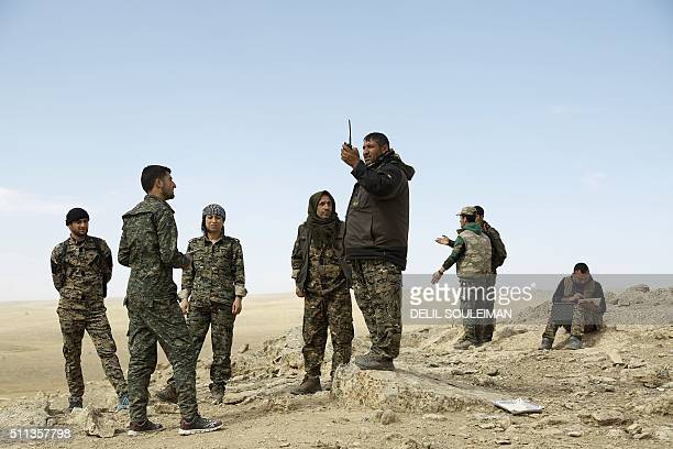 Fighters from the Syrian Democratic Forces listen to instructions as they stand on the outskirts of the town of alShadadi in the northeastern Syrian...