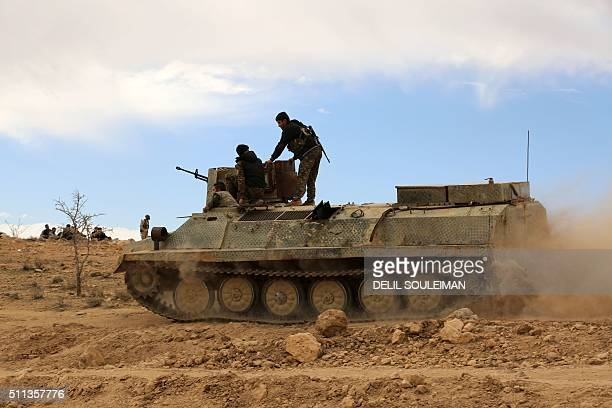 Fighters from the Syrian Democratic Forces sit atop an armoured personnel carrier on the outskirts of the town of alShadadi in the northeastern...