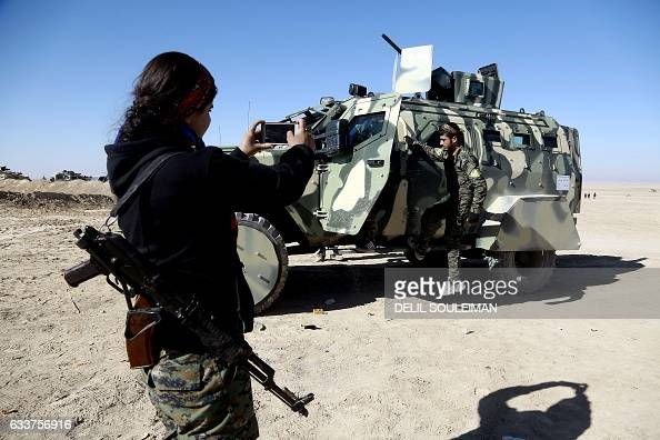 Fighters from the Syrian Democratic Forces take a picture with a military vehicle supplied by the USled coalition as they gather near a village...