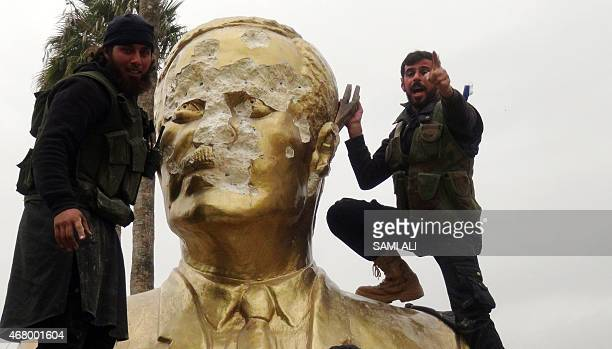 Fighters loyal to AlQaeda's Syrian affiliate and its allies smash a statue of late Syrian president Hafez alAssad father of current President Bashar...