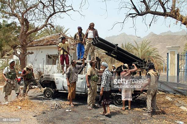 Fighters loyal to exiled President Abedrabbo Mansour Hadi stand next to a destroyed rocketlauncher belonging to Huthi rebels following clashes in...