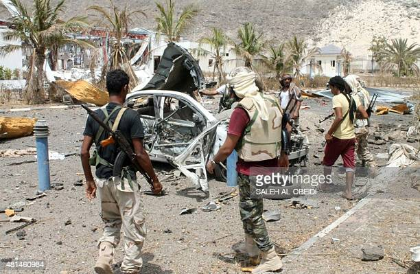 Fighters loyal to exiled President Abedrabbo Mansour Hadi stand next to a destroyed vehicles following clashes in Aden's Tawahi neighbourhood on July...