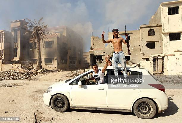 TOPSHOT Fighters loyal to Libya's internationally recognised government celebrate as they come close to seizing the centre of the eastern coastal...