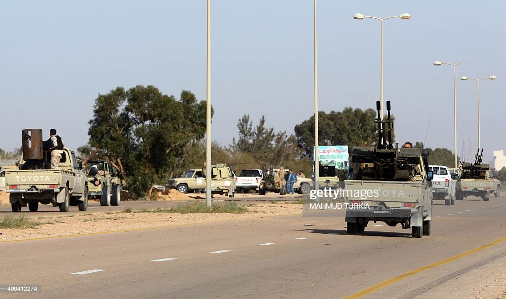 Fighters loyal to the Fajr Libya an alliance of Islamistbacked militias drive their pick up trucks on March 15 2015 in Libya's coastal city of Sirte...