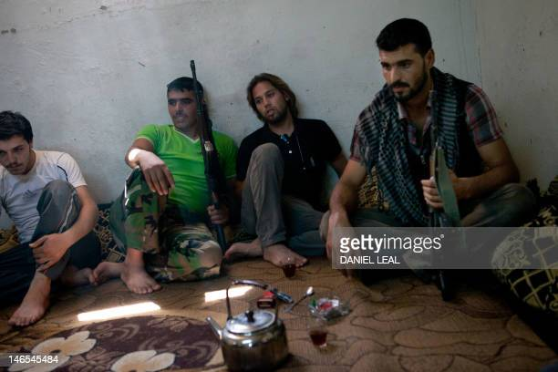 Fighters loyal to the Free Syrian Army drink tea and rest at a base on the outskirts of Idlib in northwestern Syria on June 18 2012 Syrian troops...