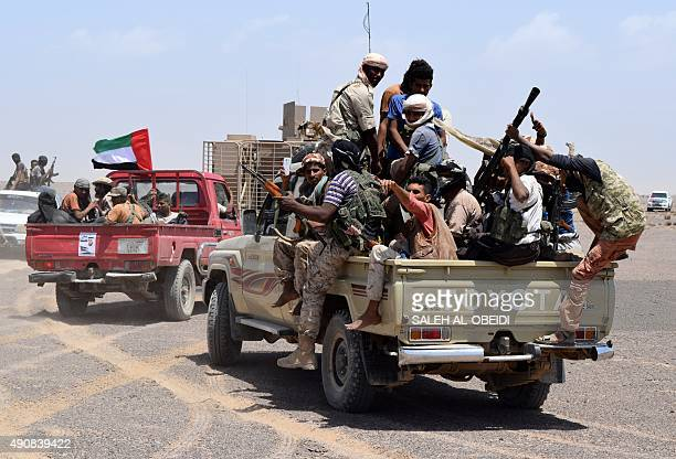 Fighters loyal to Yemeni President Abedrabbo Mansour Hadi drive in pick up truck one bearing the UAE flag in solidarity with the UAE fighters taking...
