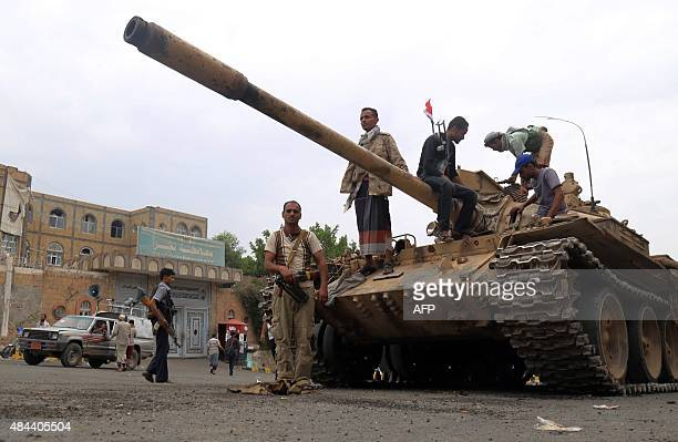 Fighters loyal to Yemen's exiled President Abedrabbo Mansour Hadi stand guard outside the gate leading to the governorate building in Yemen's third...