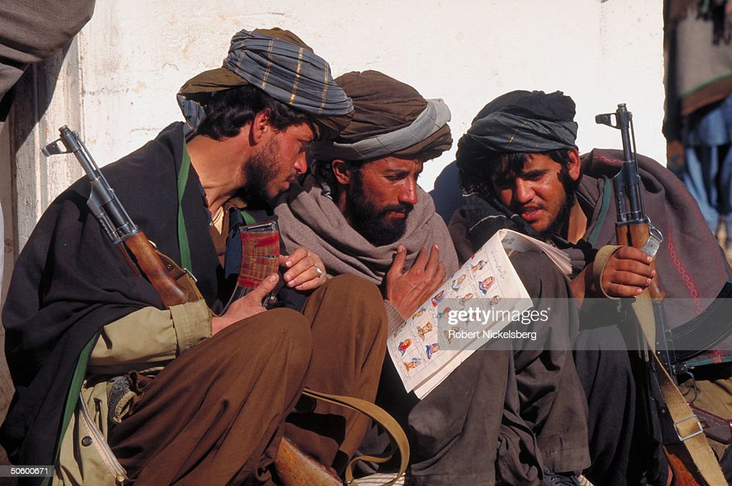 Fighters of radical Islamic cleric-led Taliban faction reading BBC bklet in Persian Dari language, at HQ of civil war-winning army outside Kabul.